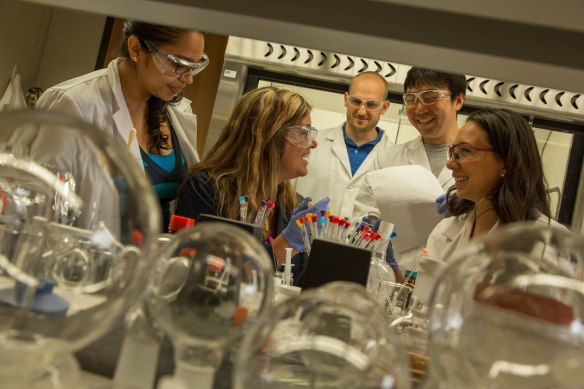 Karen Wooley (seated at center), enjoying a light-hearted moment with members of her research group between takes during a video/photography shoot in her Texas A&M Chemistry laboratory. (Credit: Robb Kendrick/Texas A&M Foundation.)