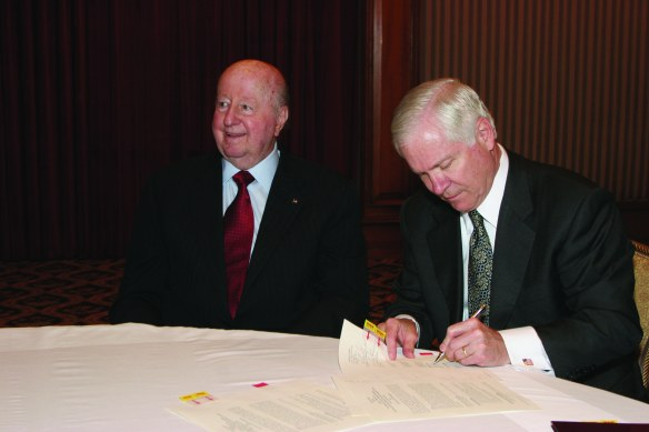 George P. Mitchell '40 and Dr. Robert Gates, signing the historic paperwork to finance construction of two landmark physics buildings at Texas A&M University.